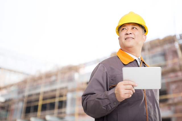 old asian man engineer with tablet and new construction site